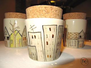 små keramikburkar med lock målade med en stad