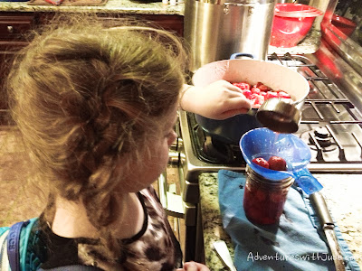pouring strawberries into canning jars