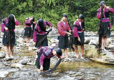 SEKUMPULAN wanita Yao Merah membasuh rambut mereka di sungai.
