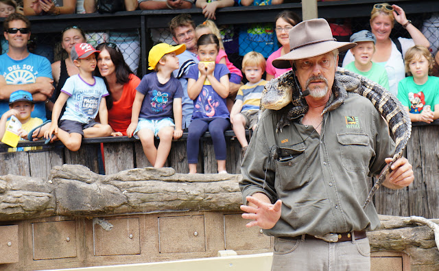 Photo of the creepy zookeeper at the park with an alligator around his neck
