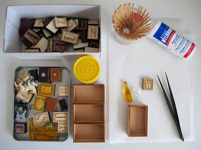 Selection of crafting supplies laid out on a table. Included are tweezers, glue, toothpicks, tiny wooden boxes, letter tiles and vintage dolls' house miniature items.