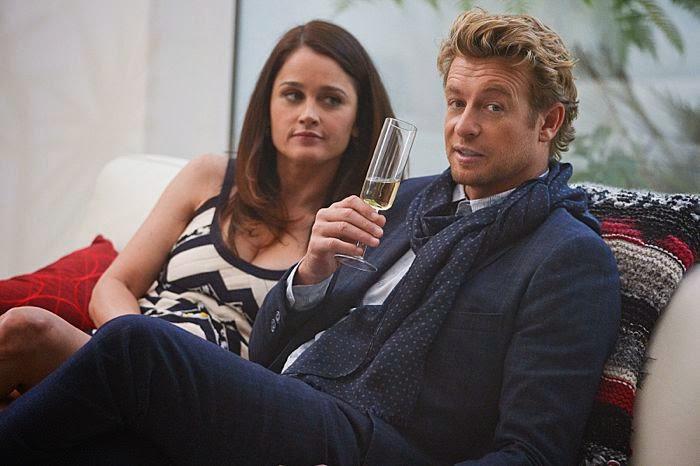 Teresa Lisbon și Patrick Jane beau șampanie așezați pe o sofa, la parterul unei vile luxoase
