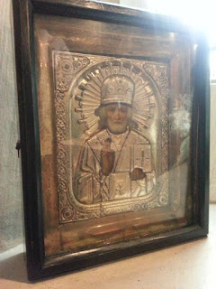 Small highly decorated religious image in wooden frame.