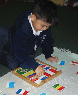 NAMC montessori student playing with world flags presenting montessori culture and science curriculum