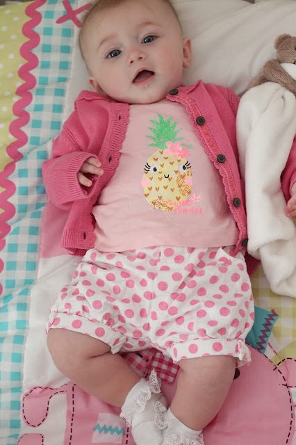 Baby girl wearing bright pink cardigan with white & pink polka dot shorts, white frilly socks and pale pink t-shirt with a glittery pineapple image