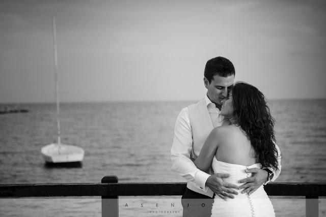 novios abrazados apoyados en puente de madera junto un barco sobre el mar