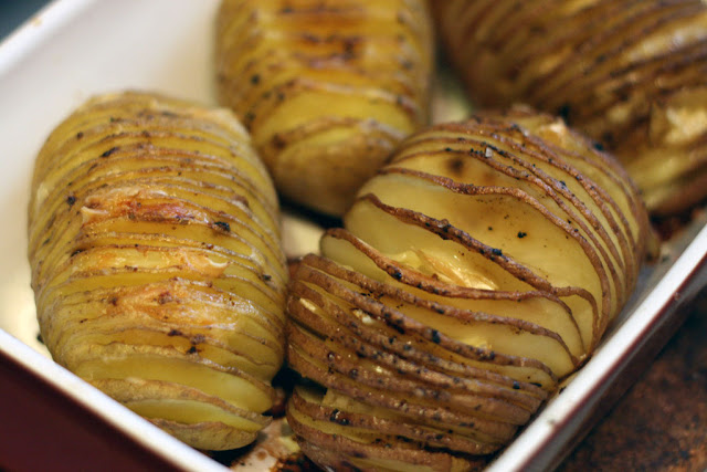 Picture of Hasselback Potatoes from above (4 of them) in a red square serving dish.