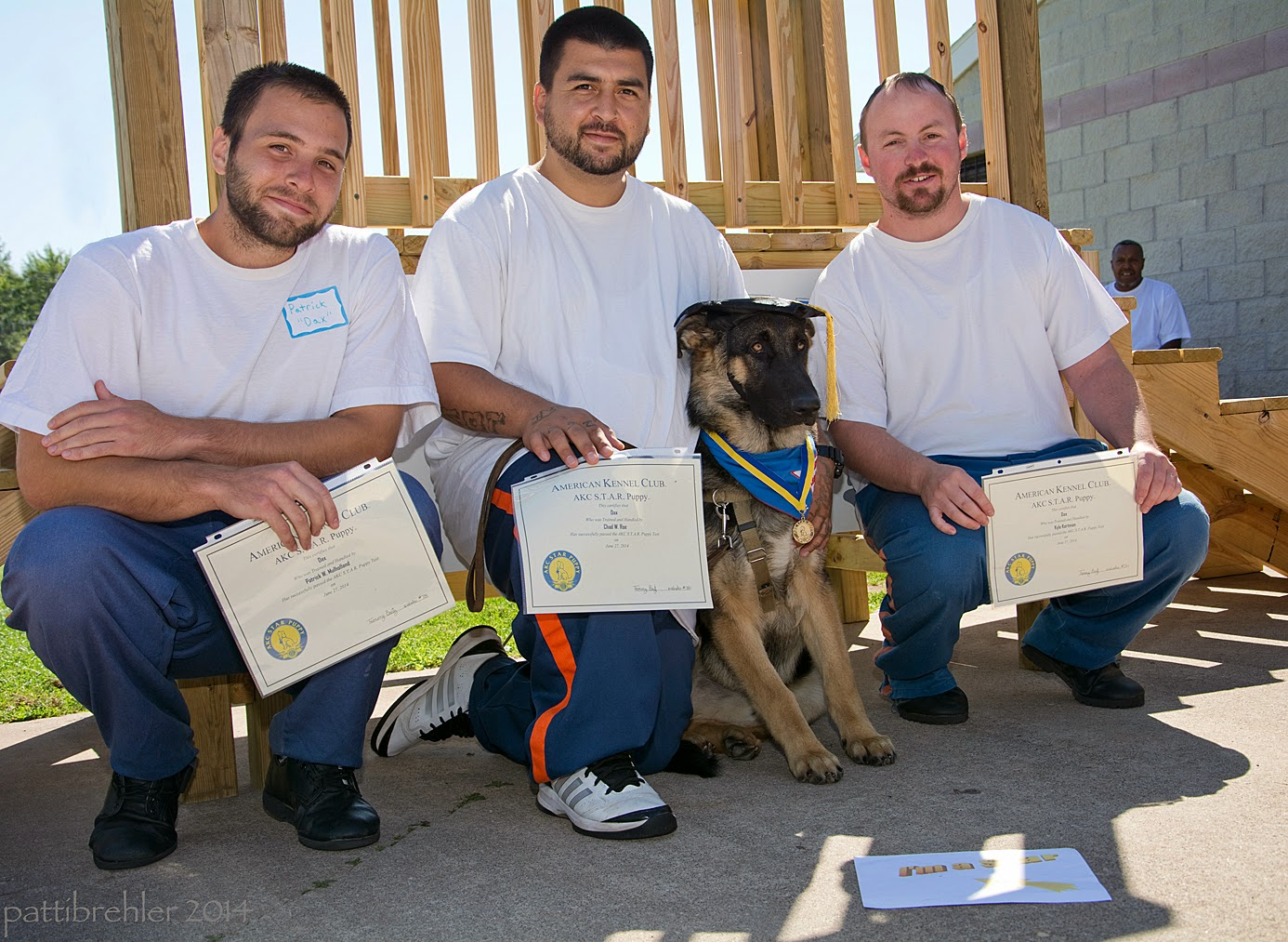 "Three men squat on cement in front of a wooden staircase, they are all wearing the blue prison pants and white t-shirts, and holding certificates up in front of their knees. Between the middle man and the man on the right a young german shepherd is sitting and leaning against the middle man, who has his left arm around the puppy. The puppy is wearing a black graduation hat, the blue Future Leader dog bandana and a medal around his neck, the dog looks like he doesn't like the hat on. A sign is lying in front of the dog, and reads ""I'm a star!"""