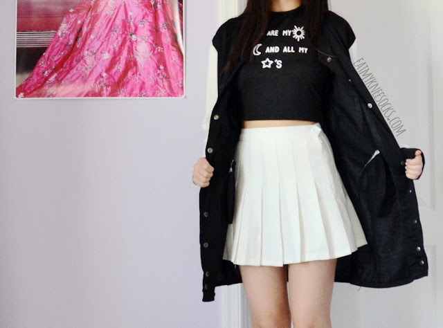 A sporty-casual monochrome black-and-white outfit, featuring Dresslink's longline baseball jacket and printed crop top, worn with a white American Apparel pleated tennis skirt.