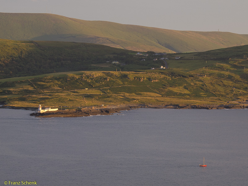 Valentia lighthouse and red sailboat