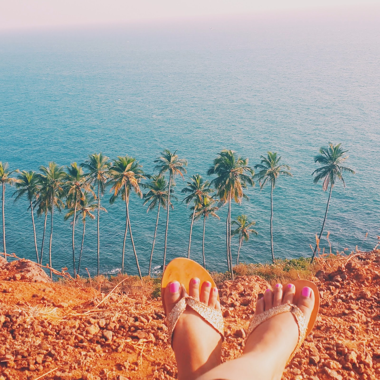 Dayle Pereira of Style File India sits with her feet in the frame wearing gold sandals and pink nail polish on a cliff overlooking a coconut palm tree dotted terrain near the ocean