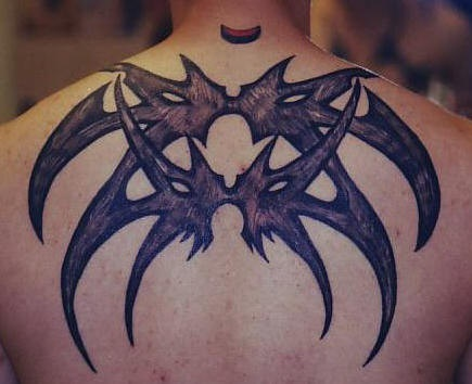 Tribal spider tattoo on upper back