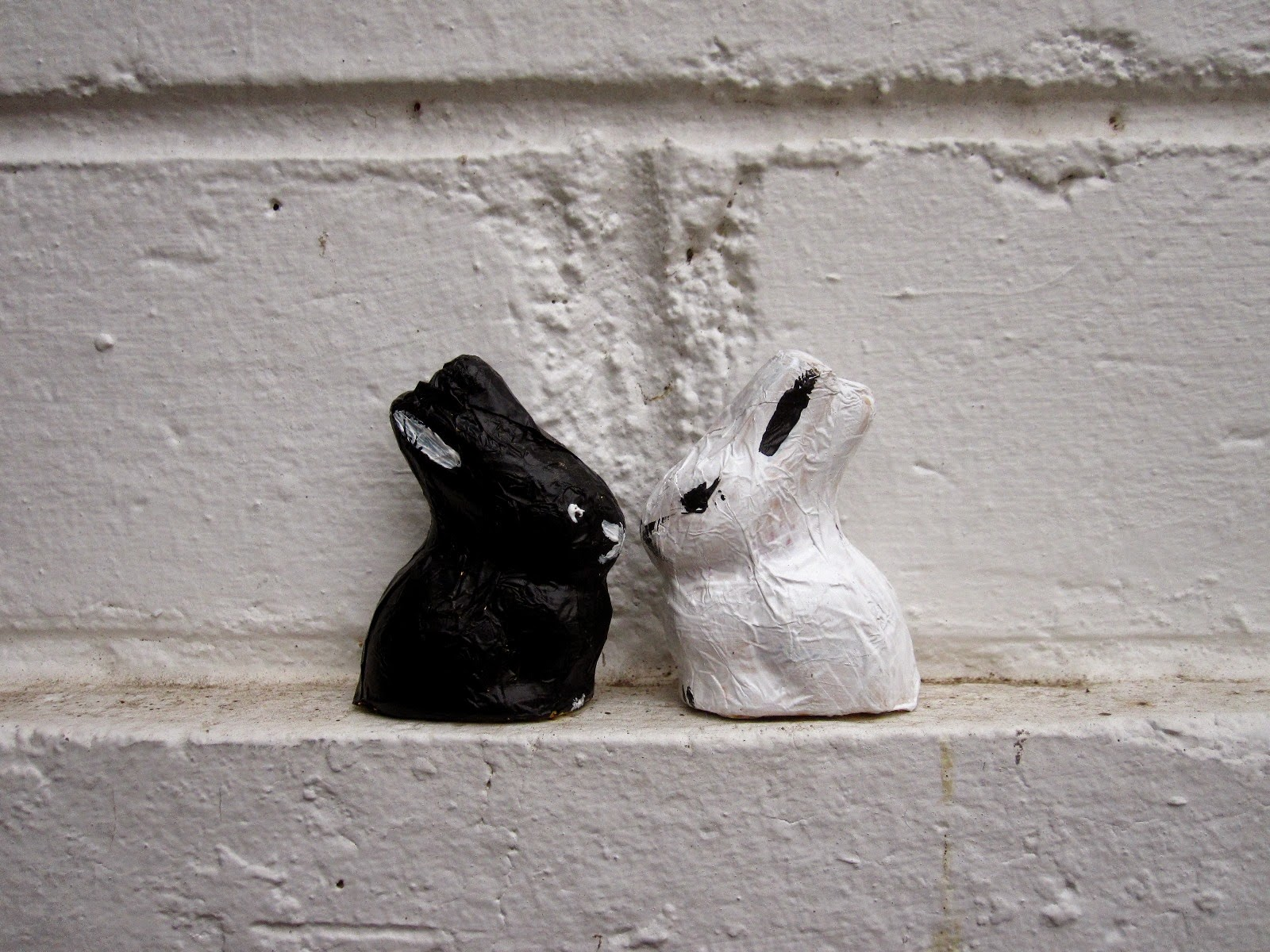 Two foil-covered chocolate bunnies sitting on a white wall. One has been painted black, the other, white.