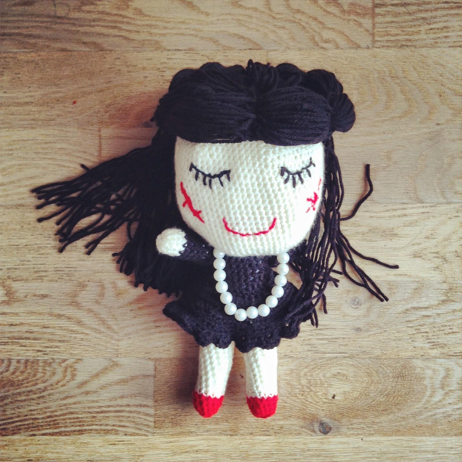 poupée au crochet avec un collier de perles