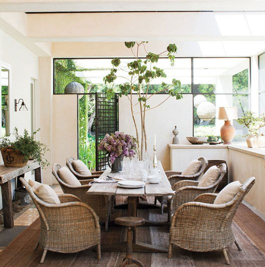 covered enclosed sun porch in t.v. star Ellen Degeneres' home with a rustic dining table surrounded by wicker arm chairs.