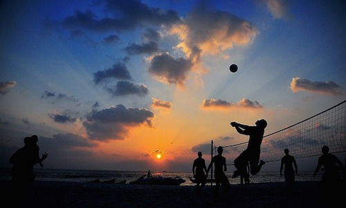 People playing volleyball on the beach as a fun exercise