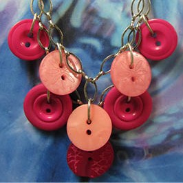 Necklace has layers of pink buttons hanging pendant style from silver chain