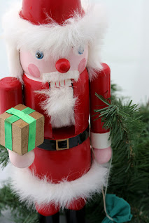 A Santa nutcracker nestled in pine branches against a white background