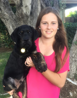 Megan smiles holding a young guide dog puppy (black and brindle Lab).