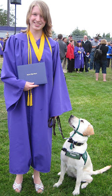 Miranda in cap and gown with yellow Lab puppy