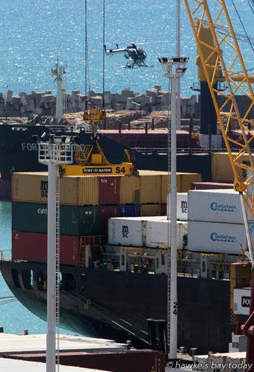 Helicopter flies over container ship to land on the wharf at Napier Port photograph