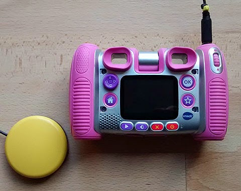 Kiddizoom Twist Plus, switch adapted for use with accessibility switch. (Pink camera and yellow switch). Rear view of camera.