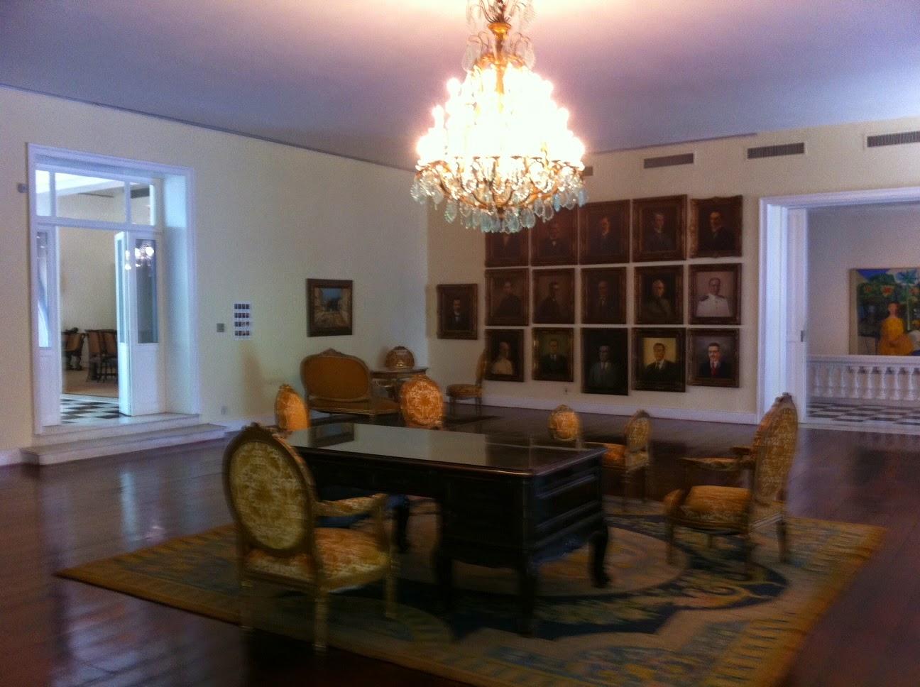 Descrição da foto: um dos salões principais, na parede ao fundo várias pinturas, no centro uma grande mesa de madeira escura com cadeiras estofadas em volta, um grande tapete no chão. No teto um candelabro de cristal.