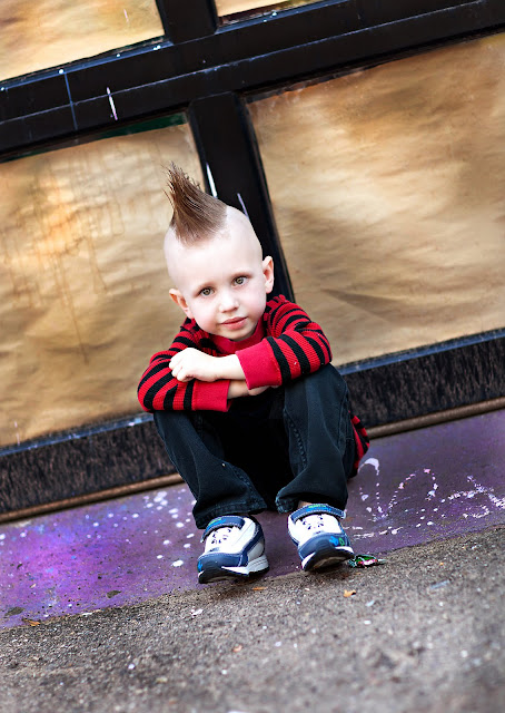 Rocker child stares into the camera of a Tucson photographer with an urban background