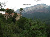 En primer terme una de les cases del nou Sant Romà de Sau i al darrere els Cingles de Tavertet