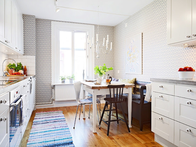 Alternative view of the kitchen in a tiny apartment with chandelier, geometric wallpaper, white cabinets and drawers, a cozy breakfast nook with a bench and mismatched chairs a wood floor and a striped rug