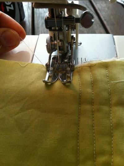 sujetad los hilos hacia atrás antes de empezar a coser