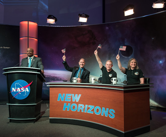 NASA Senior Public Affairs Officer Dwayne Brown, standing left, closes a New Horizons media briefing as NASA Associate Administrator for the Science Mission Directorate John Grunsfeld, seated left, New Horizons Principal Investigator Alan Stern of Southwest Research Institute (SwRI), Boulder, CO., center, and New Horizons Mission Operations Manager Johns Hopkins University Applied Physics Laboratory (APL) Alice Bowman wave the American flag shortly after the New Horizons spacecraft's closest approach to Pluto, Tuesday, July 14, 2015 at the Johns Hopkins University Applied Physics Laboratory (APL) in Laurel, Maryland. Photo Credit: (NASA/Bill Ingalls)