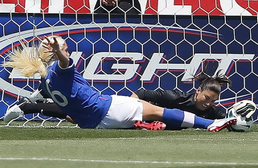 USA goalkeeper Hope Solo blocks the shot of Canadian player Kaylyn Kyle