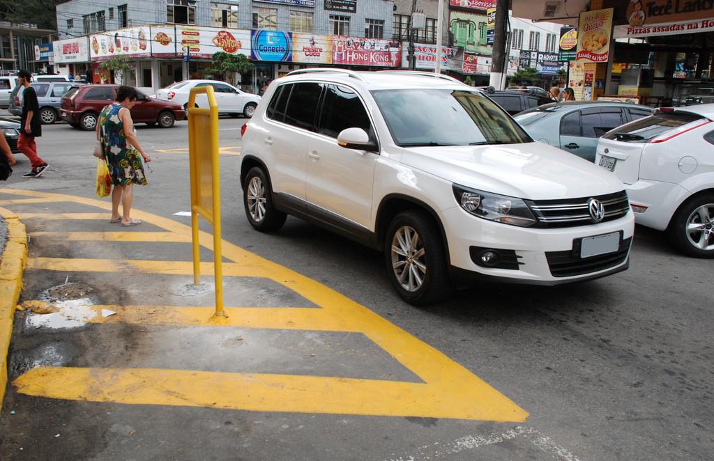 Área em torno do obstáculo sinalizada em amarelo, na entrada da Rua Duque de Caxias, alerta para a proibição de estacionar no local