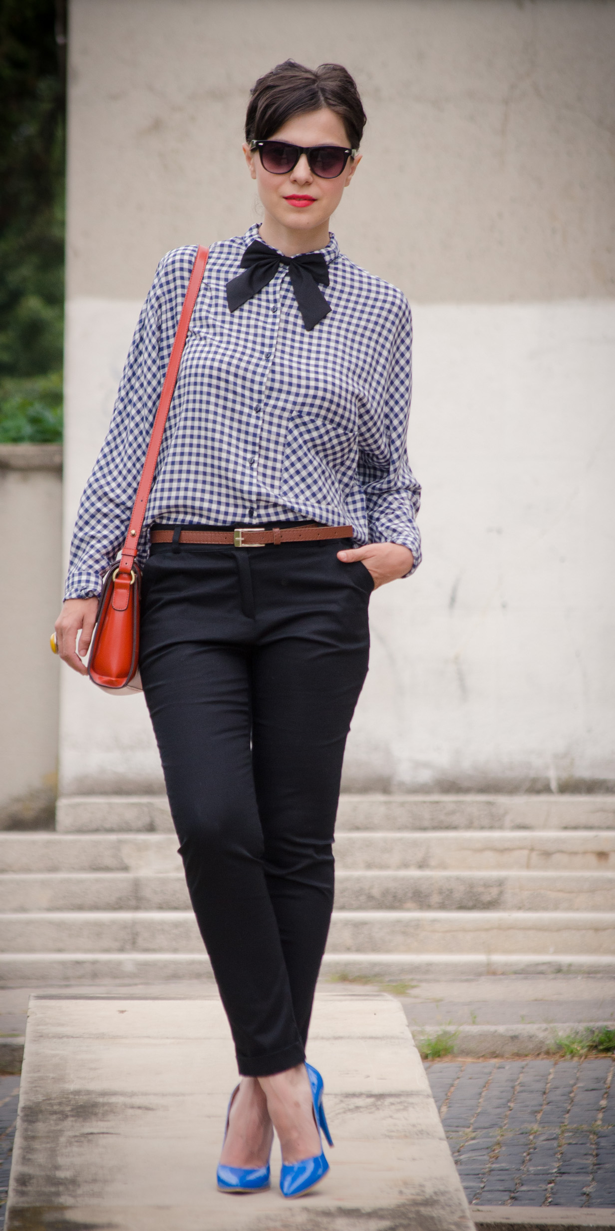 preppy back to school outfit checkers shirt navy blue heels orange satchel black bow tie black pants