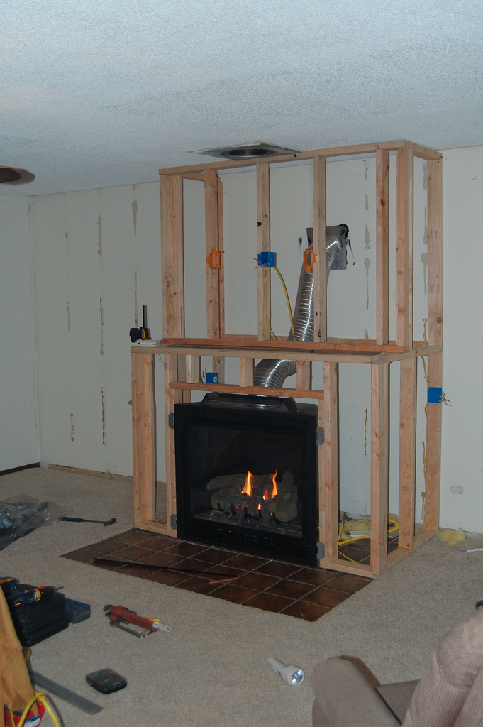 Remodelaholic amazing diy fireplace and built ins for Building a corner fireplace