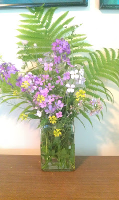 White, purple, and yellow flowers in a vase with ferns.