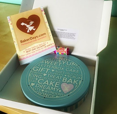 Morgan's Milieu   Baker Days Letterbox Cake Review: Blue tin with writing on top inside a white box.