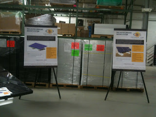 Stacks of solar equipment behind display boards