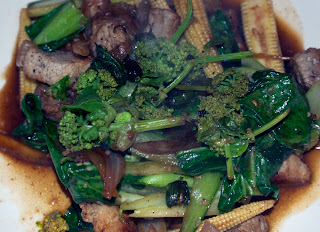 Stir fry of pork and baby sweetcorn with wild alexanders flowers and wild dandelion flower buds
