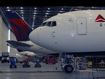 Aviões da Delta protegidos dentro do centro de reparo.