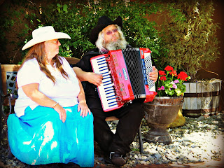 A man plays accordion and woman sings at the Founder's Day event in Albuquerque's Old Town