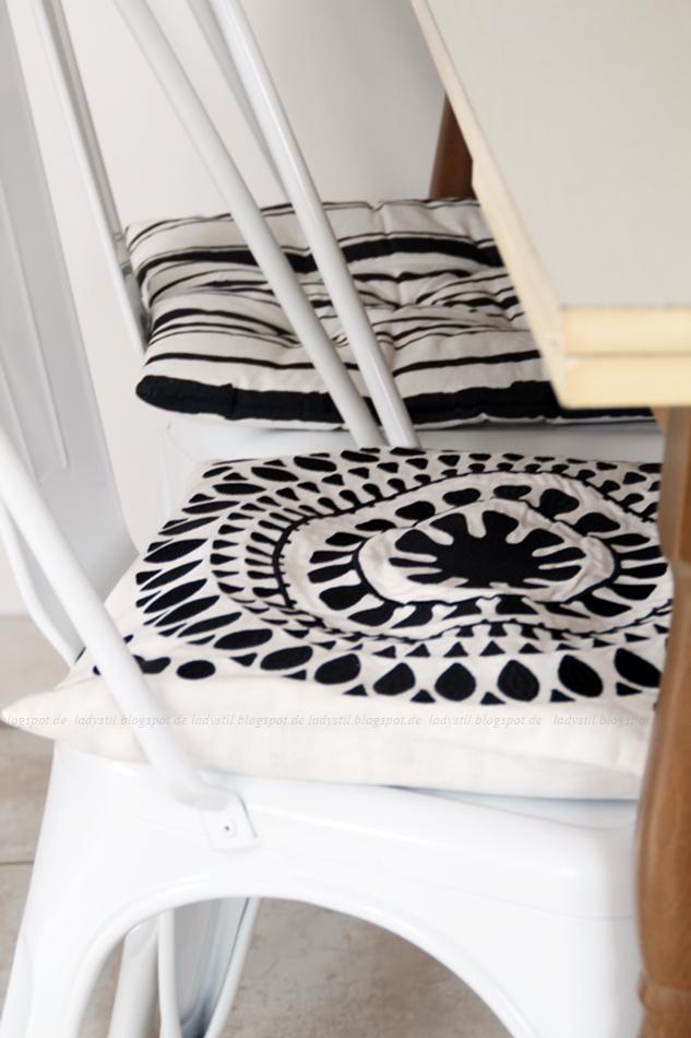 schwarz weiße Stuhlkissen auf weißen Tolix Stühlen
