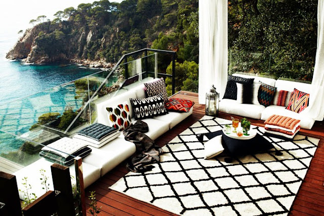 deck patio cliff cliffside ocean sea view outdoor living room moroccan rug built in furniture