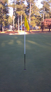 yellow golf pin flag on a green