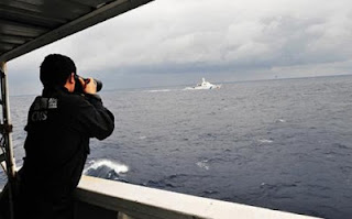 A China Marine Surveillance officer photographs a Japan Coast Guard vessel near the disputed Diayou Islands last week. Photo: Xinhua