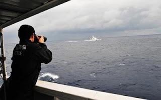 A China Marine Surveillance officer photographs a Japan Coast Guard vessel near the disputed Diayou Islands last week. Photo: Xinhua