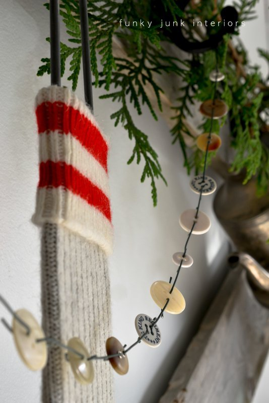 A Christmas decorated headboard with an evergreen and button garland via Funky Junk Interiors