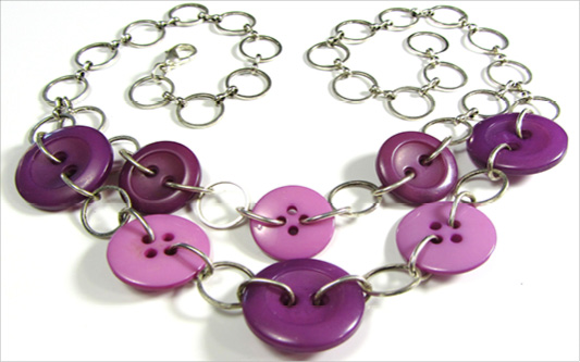 Double strand necklace has purple buttons linked with silver chain