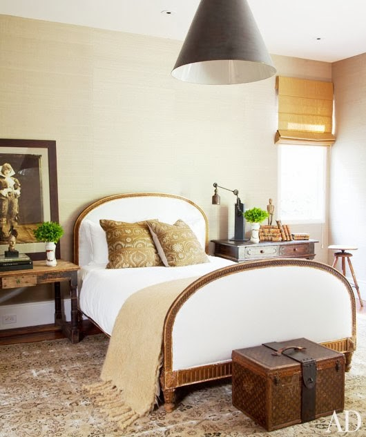 Bedroom with a Louis Vuitton Trunk at the foot of the bed and a large cone shaped pendant light